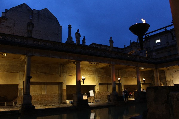 The Roman baths lit up by torches