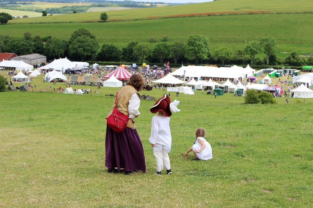 Three people standing on a hillside looking down at the history festival in the valley