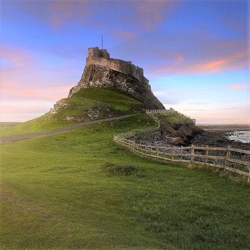 Lindisfarne from a distance showing a castle on top of a hill.
