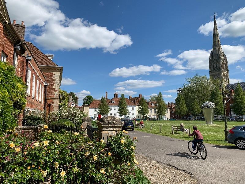 A boy on a bike cycling around Choristers Green in Salisbury in the sunshine.