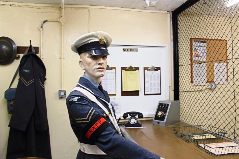 A mannequin in guards uniform at a desk