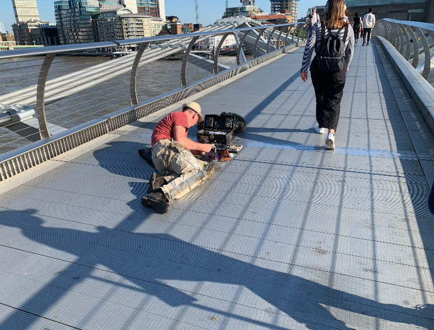 A man lying on his front painting the Millennium Bridge
