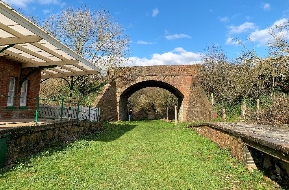 A disused railway station and a railway bridge with grass instead of train tracks