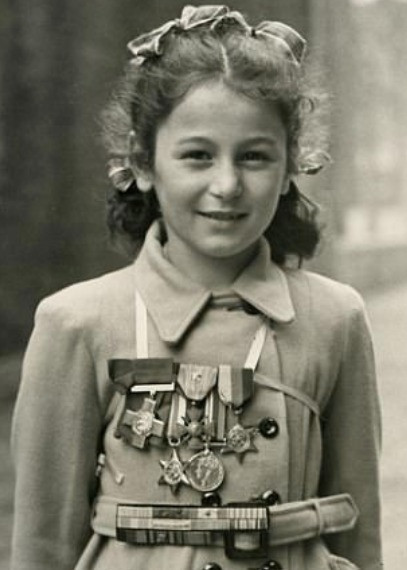 A black and white photo of Tania Szabo collecting her mothers medals at the age of 4.