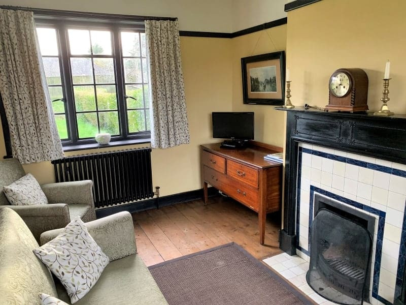The sitting room in the Vintage House showing authentic furniture and a fireplace.