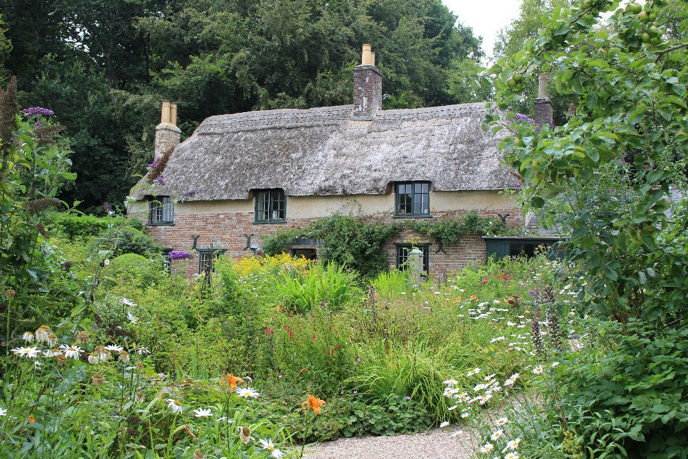 A thatched cottage surrounded by a garden filled with flowers