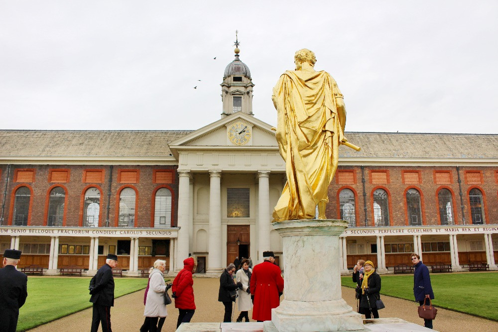 A golden statue surrounded by a tour group and a Chelsea Pensioner
