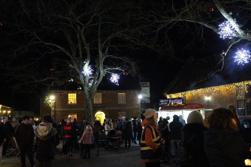 Crowds and fast food stalls uder a tree with Christmas lights