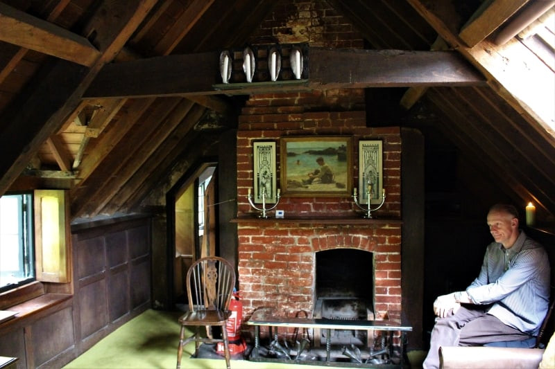A guide sitting in the upstairs room next to the fireplace.