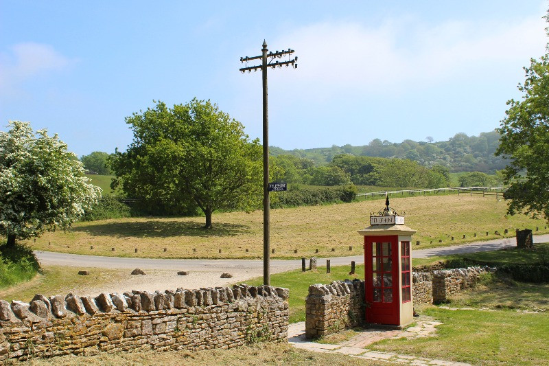 A old telephone box and telegraph pole in the abandonned village of Tyneham
