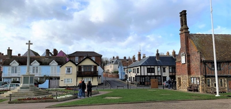 A memorial cross, houses and the timber framed Moot Hall in Aldeburgh.