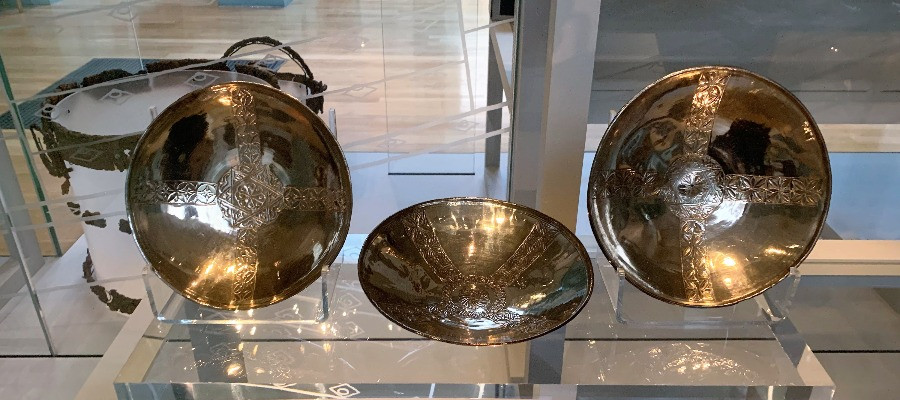 Three silver bowls in a display case