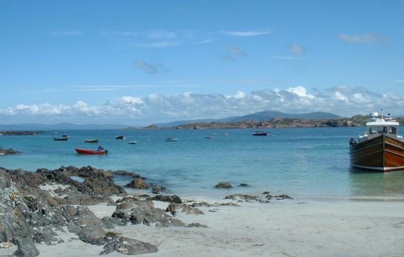 A boat on the blue sea and rocky coastline of Iona