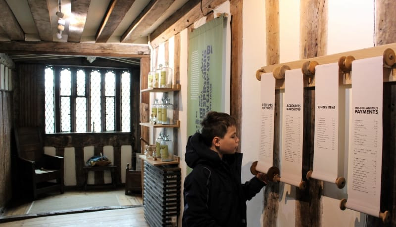 A boy reading scrolls on the wall inside the Guildhall museum.