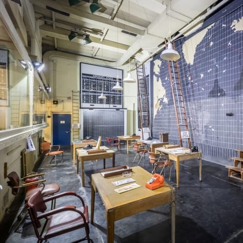 A wall map, chairs and tables inside a room at the Liverpool bunker.