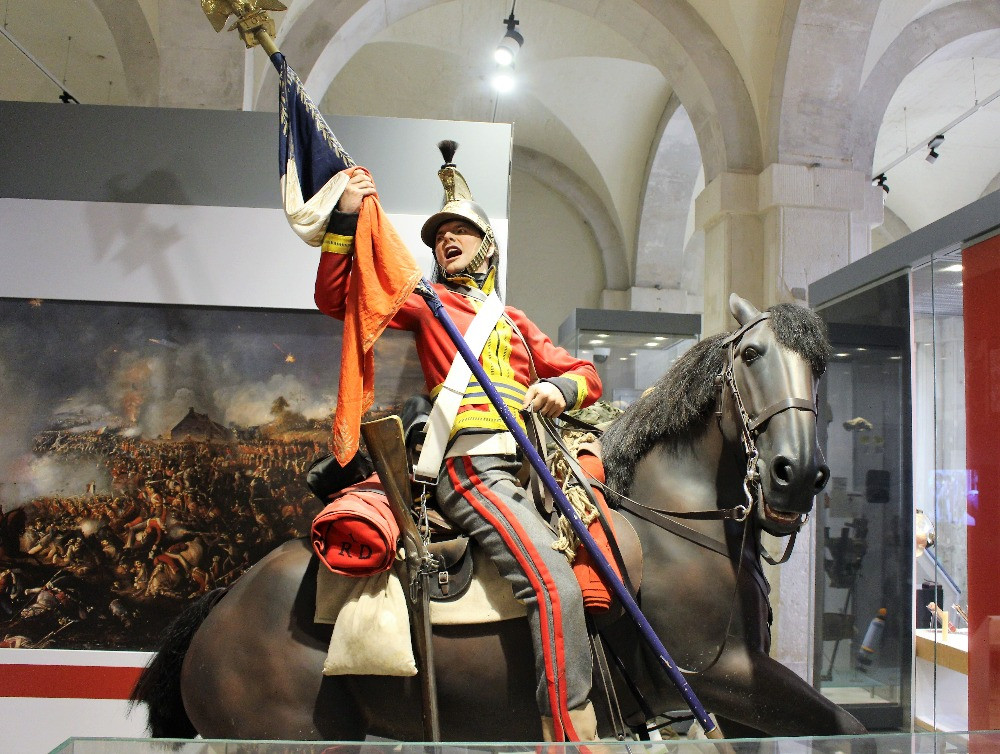 A manequin of a soldier on horseback waving a flag at the Battle of Waterloo i the Hosehold Cavalry Museum.