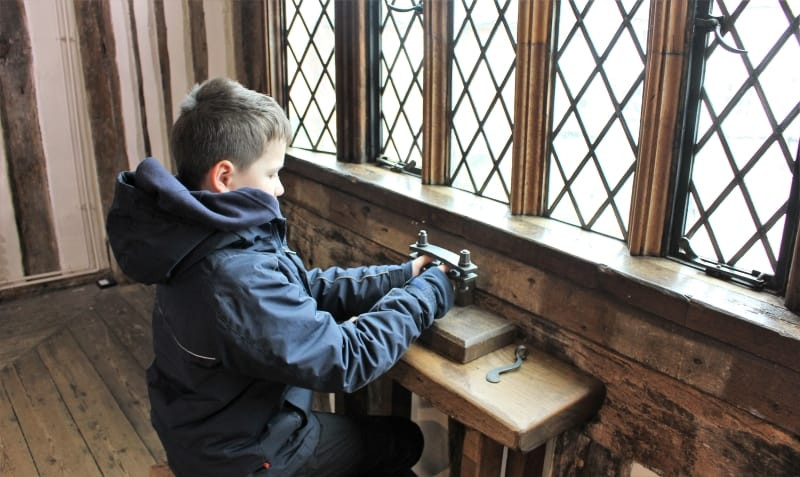 A boy trying out thumbscrews in the museum.
