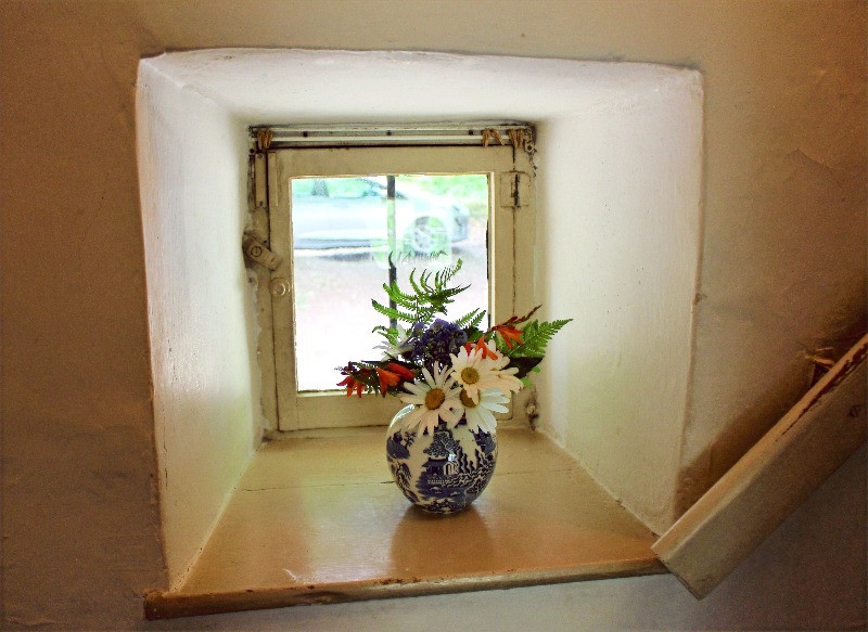A small window with thick walls and a vase of flowers on the sill