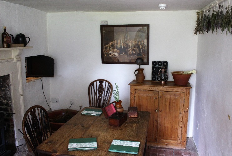 A tiny parlour with a large fireplace, table and chairs