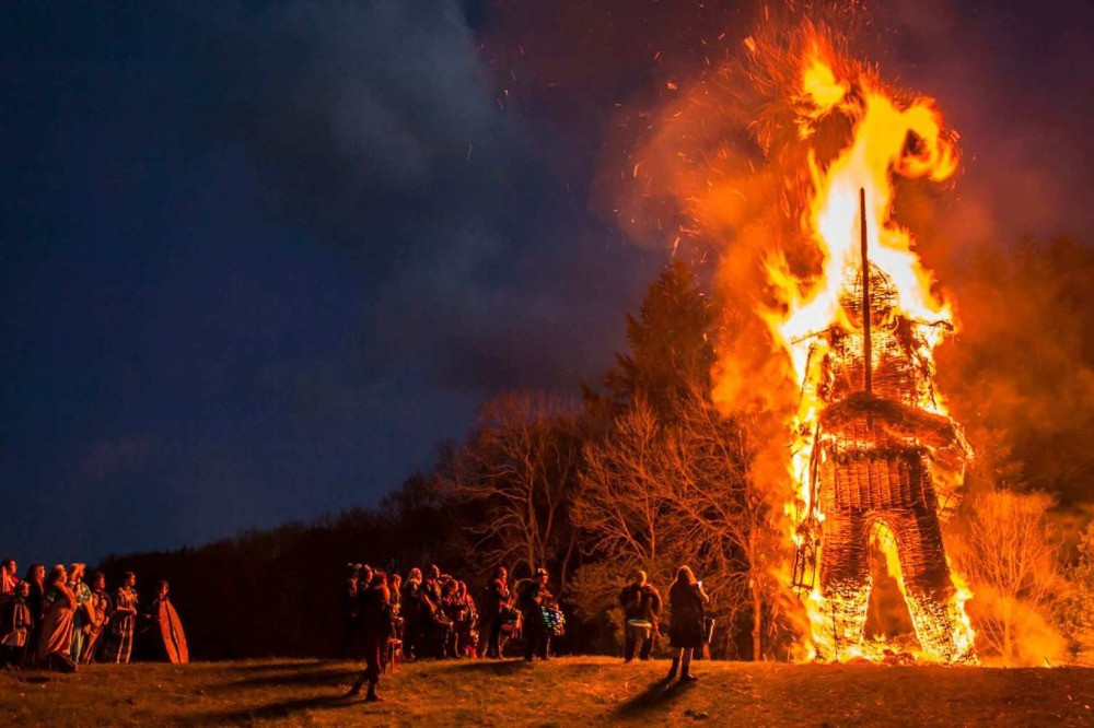 A group of people gathered around as a giant wickerman burns