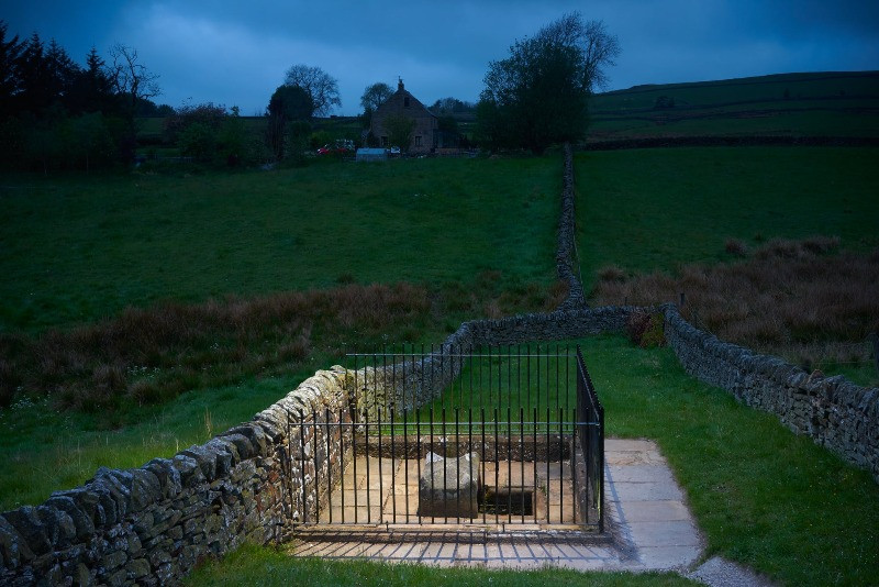 Mompessons well in the village of Eyam surrounded by a stone wall and railings