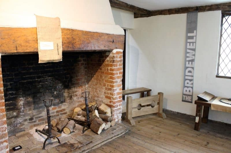 The stocks in the corner of the room next to a brick fireplace.