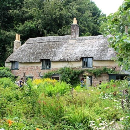 thomas Hardy's cottage surrouded by a verdant cottage garden.