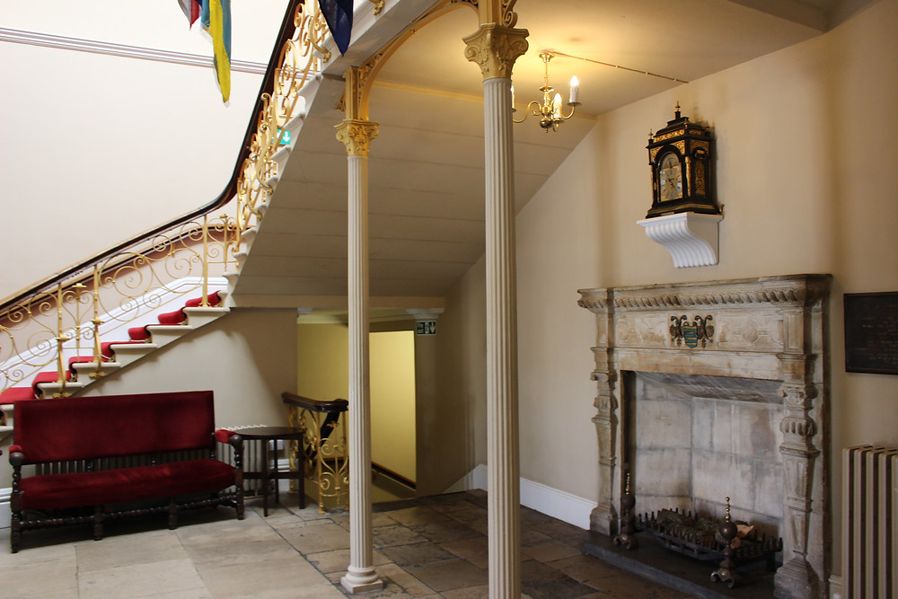 A old stone fireplace underneath a large staircase.