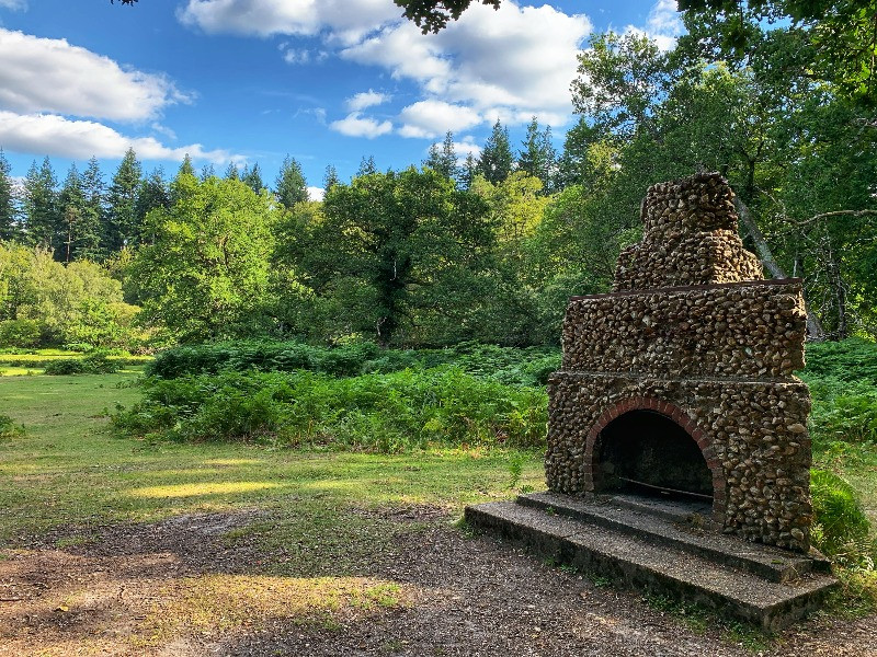 The Portuguese fireplace in the New Forest against a backdrop of trees.