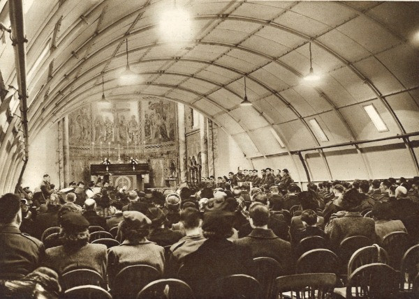 A black ad white photo of the congregation sitting down for a service inside a Romney hut in the bombed out shell of the chapel.