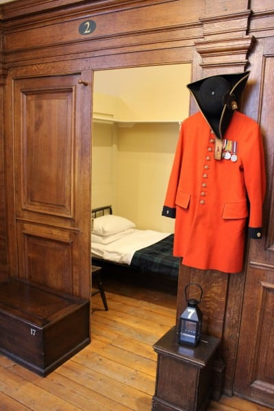 One of the original berths with a Chelsea Pensioner uniform hanging outside it