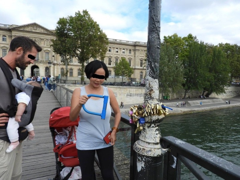 A woman attaching a huge bike lock to the Pont des Arts