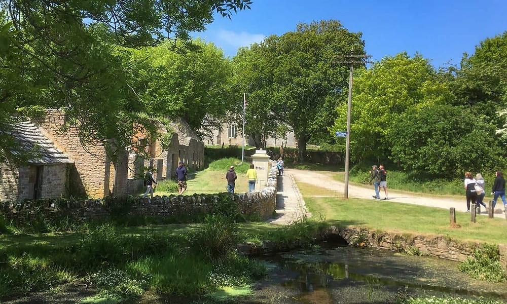 People walking amongst the ruins of Tyneham