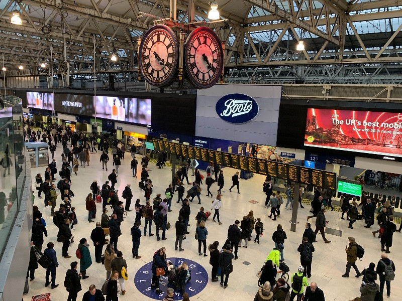 Crowds of people in Waterloo Station looking at the timetables