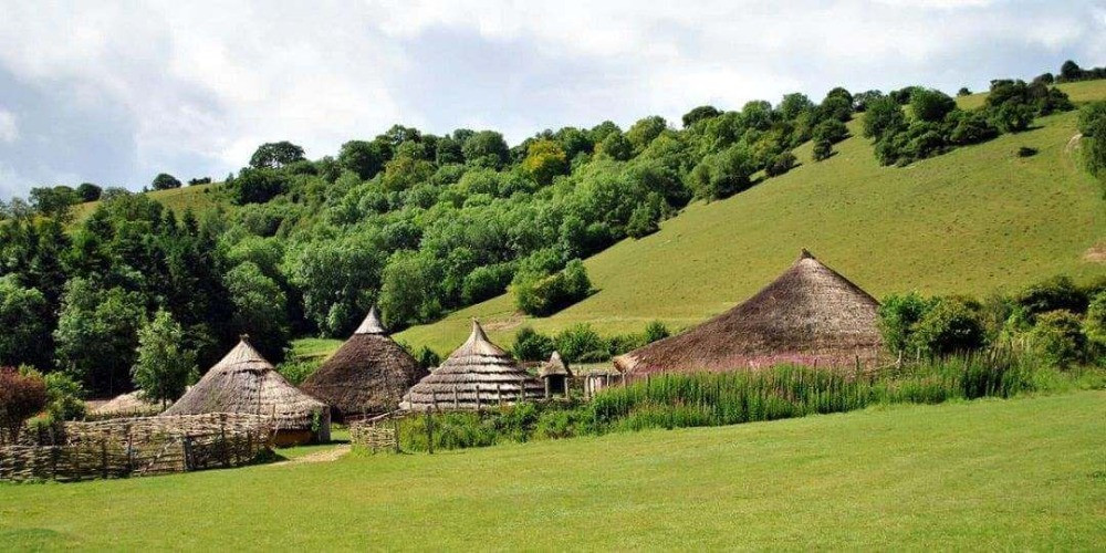Thatched roofs of the roundhouses in a green valley at Butser Ancient Farm