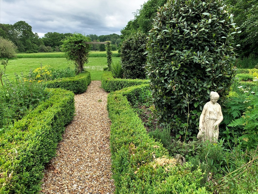 A formal garden with a statue and hedges