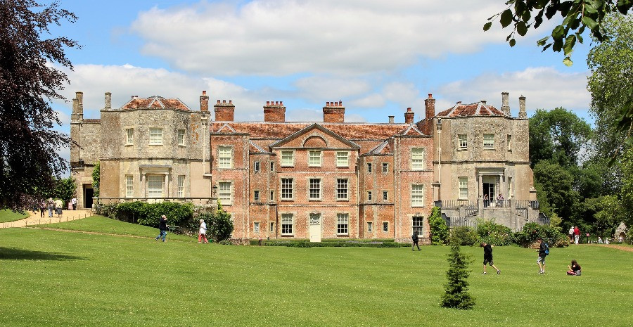 People walking on the frot lawn with Mottisfont House in the background