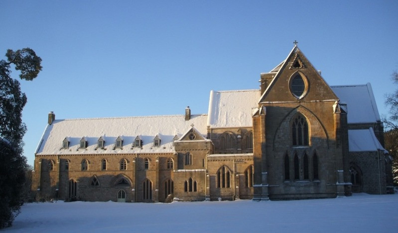 The exterior of Pluscarden Abbey covered in snow