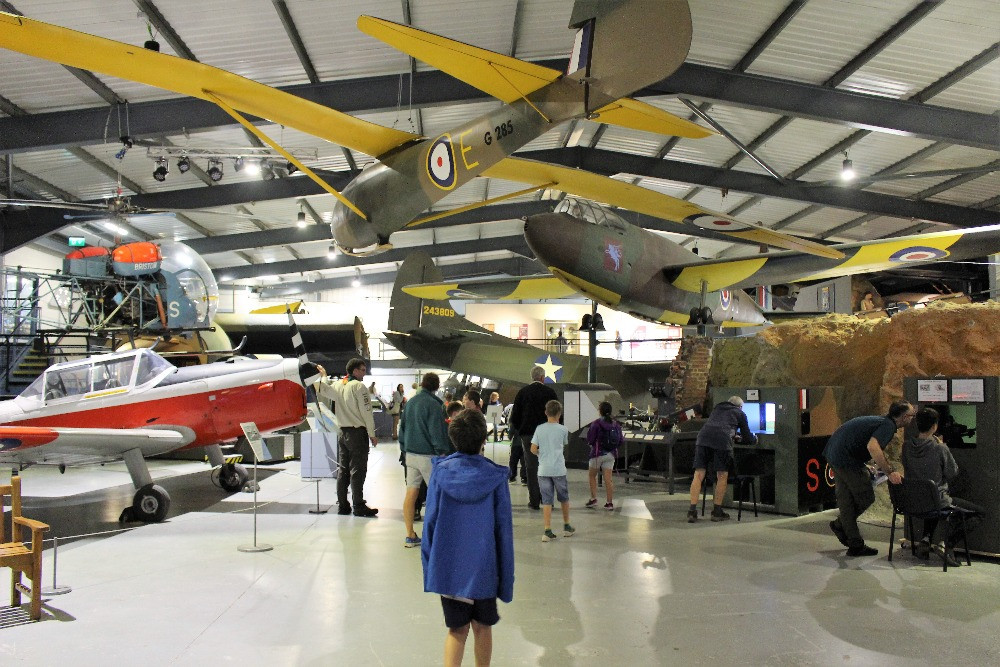 A boy looking at aircraft hanging from the ceiling in a large hangar