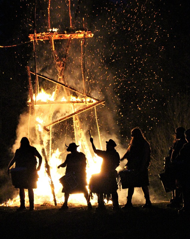 The wickerman nearly burnt, with drummers in silhouette at the base