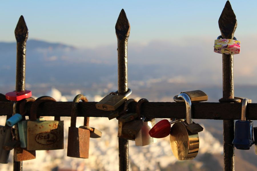Padlocks attached to a fence with a view over Santorini