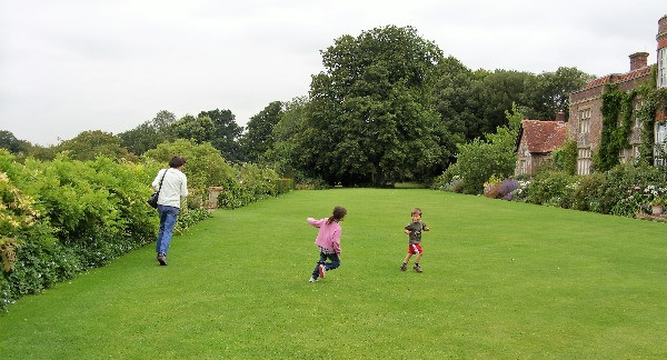 Kids running around the grounds of a stately home