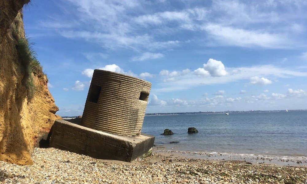 A round concrete block lop sided on a beach with the sea behind it.