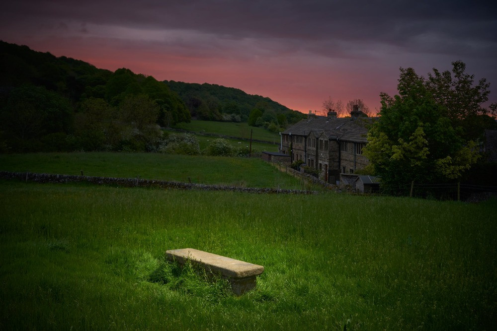 A single table grave on a hillside behind some cottages.