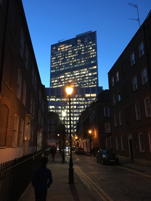 A modern office block towering over a Georgian road.