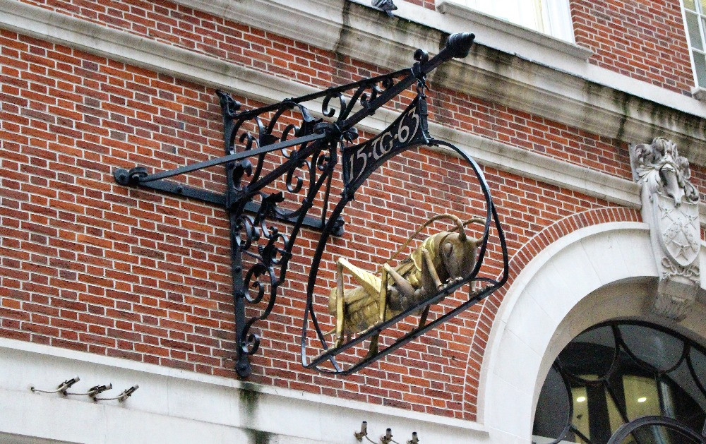 The golden grasshopper sign hanging from a brick wall.