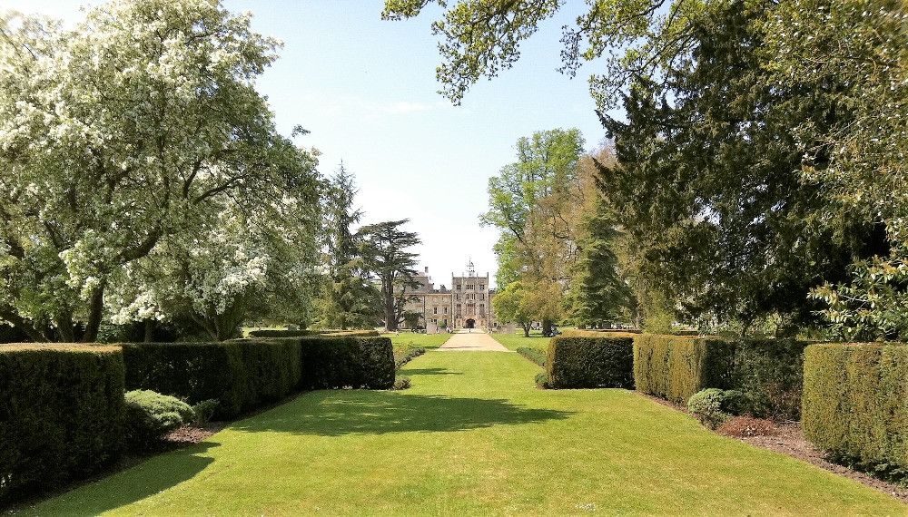 Wilton House in the far distance behind some trees and lawns