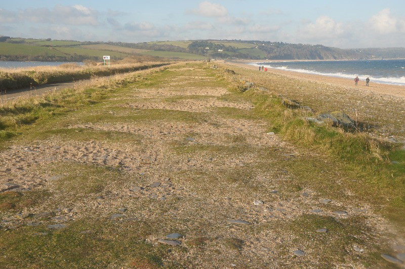 A long stretch of grassy beach with sea on either side.