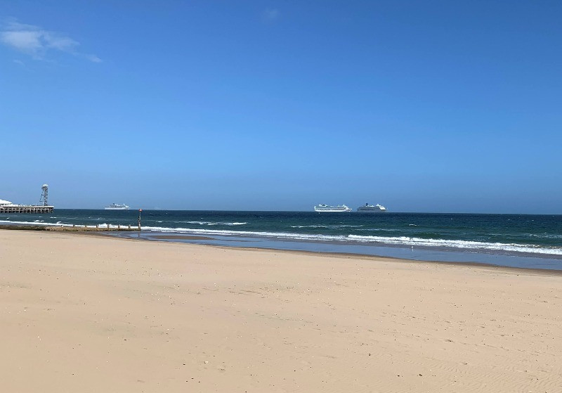 Cruise ships in the distance of Bournemouth beach with golden sand and blue sea and sky