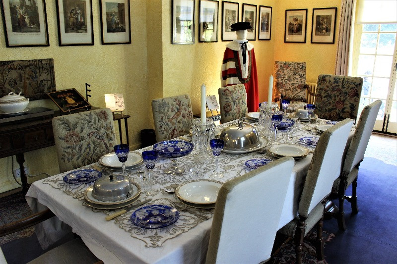 The dining table laid out for a meal, with his baroncy robes on a mannequin next to it.